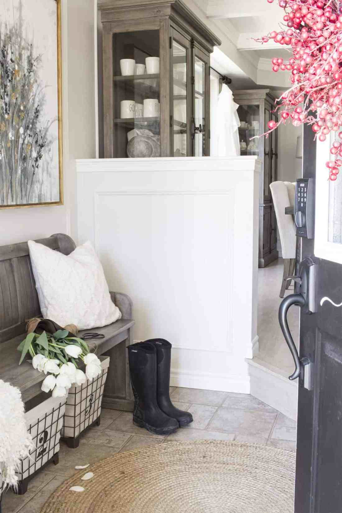 farmhouse style entryway with church pew style bench, numbered wire baskets underneath, etc
