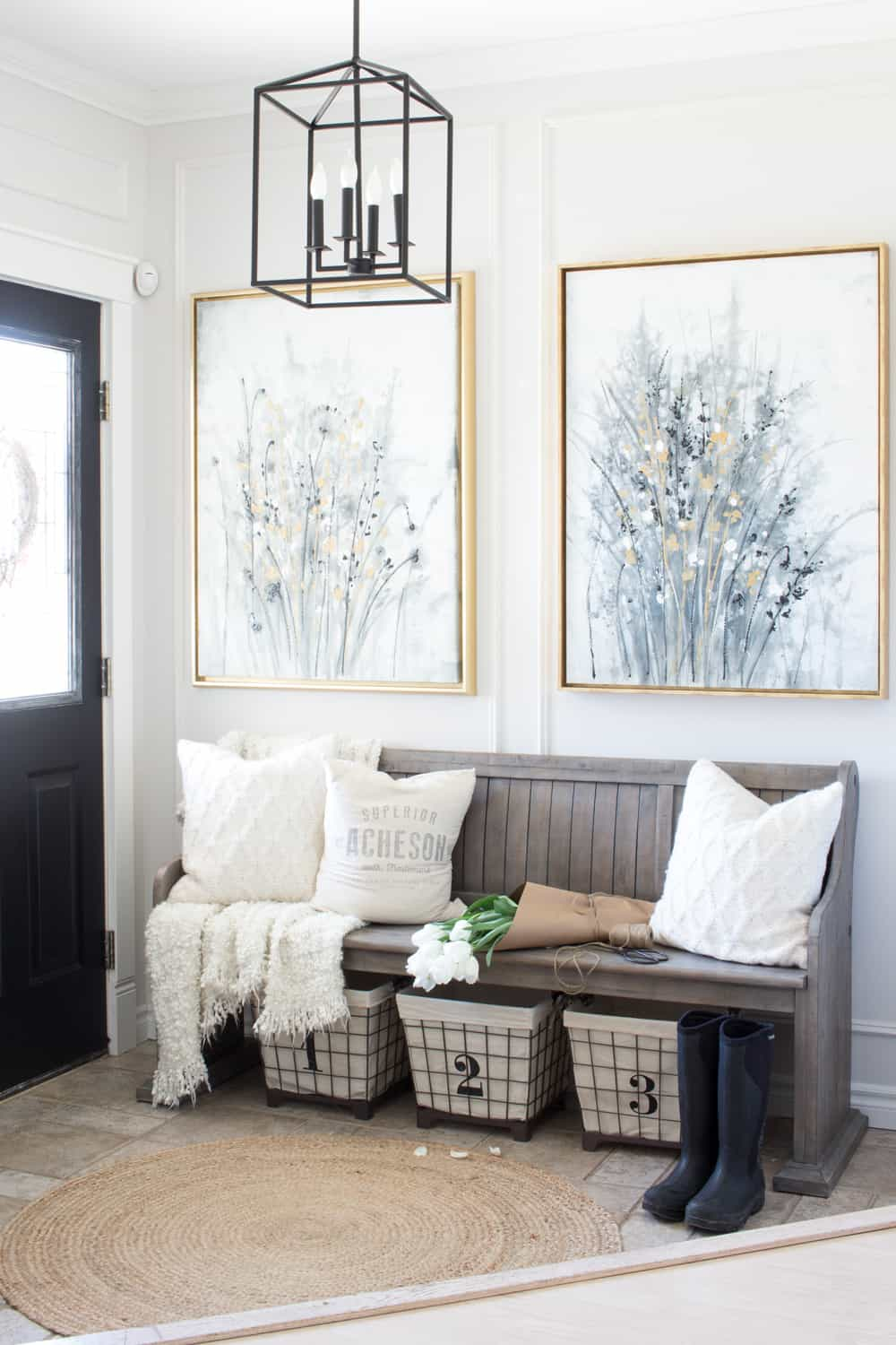 Farmhouse style entry with church pew style bench, art, numbered wire baskets