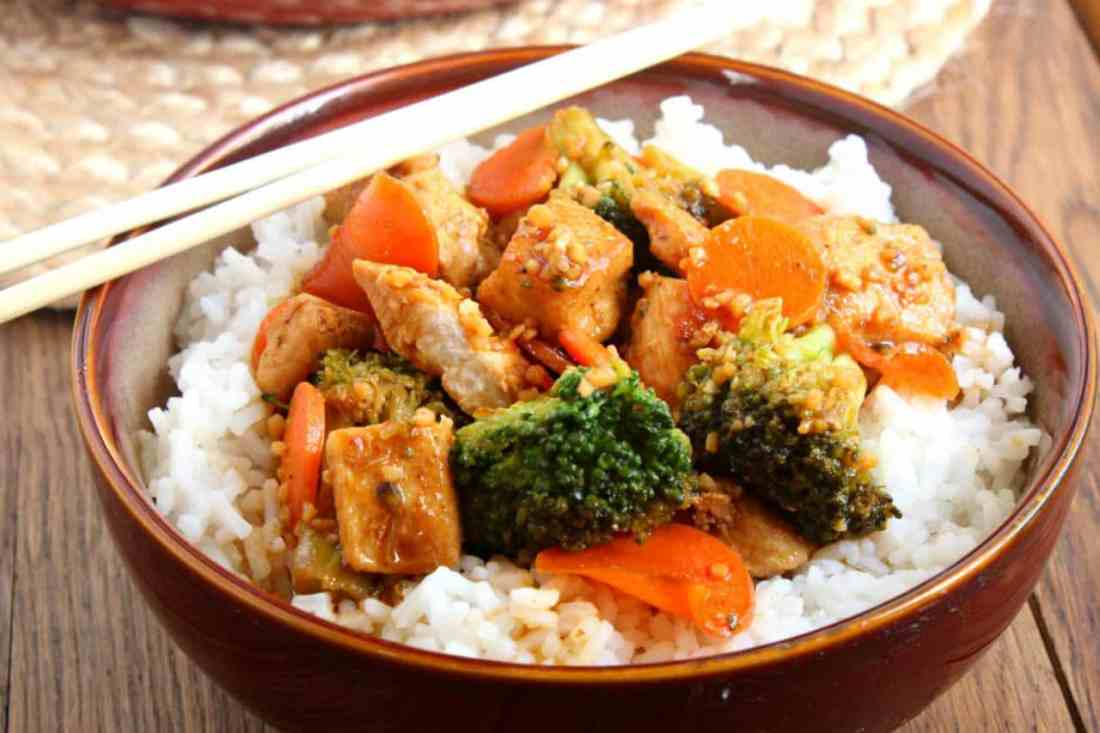 honey garlic stir fry in a red bowl with rice and chopsticks