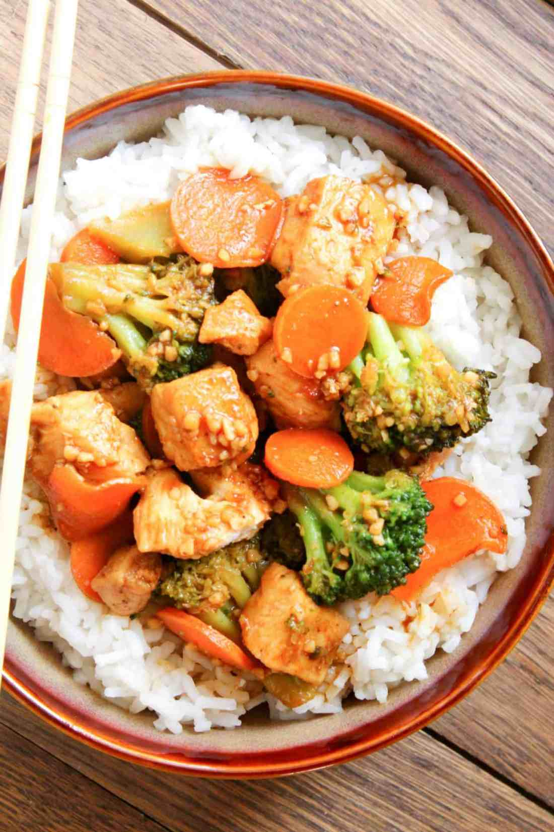 honey garlic chicken with broccoli and carrots on a bed of rice on a red bowl
