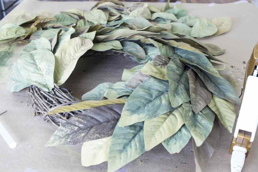 gluing magnolia leaves on grapevine wreath