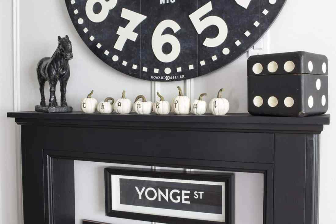 black mantel with white baby pumpkins thankful