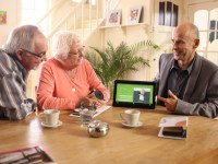 Home Mobility consultant discussing with man and woman, tablet screen