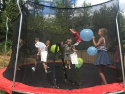 The kids jumped on the trampoline with their ironman rings and balloons.