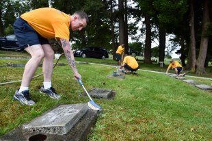 160816-N-OO032-009 BREMERTON, Wash. (Aug. 16, 2016) – Chief Aviation Electronics Technician (Select) Adam Ericsson, from Des Moines, Iowa, and stationed with Electronic Attack Squadron One Two Nine (VAQ-129) Vikings, clean head stones with fellow Pacific Northwest chief petty officer selects during a community relations event at Ivy Green Cemetery as part of the USS Turner Joy (DD 951) Legacy Academy. The academy entails living aboard the Vietnam-era destroyer while participating in community relation projects, ship preservation, leadership training, and a naval heritage capstone project. The Turner Joy is one of four naval memorial in the U.S. to host legacy academies, the other three being the Iowa-class battleship USS Missouri (BB 63), USS Midway (CVB/CVA/CV 41) and USS Constitution, a wooden hulled, three-masted heavy frigate and oldest commissioned warship in the world. (U.S. Navy photo by Mass Communication Specialist 1st Class Cory Asato/Released)