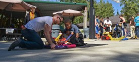 SILVERDALE, Wash. (Aug. 12, 2016) – Nathan Laurie, an intern with the Navy's Strategic Systems Programs, assists a child, enrolled in the Bangor School Age Care Program, with launching his pneumatic rocket during a STEM outreach project coordinated by Naval Sea Systems Command and Puget Sound Naval Shipyard and Intermediate Maintenance Facility. The Navy is actively seeking candidates well versed and qualified in STEM through programs such as the Navy Reserve Officers Training Corps, the Naval Academy, the Nuclear Propulsion Officer Candidate Program and the Civil Engineer Collegiate Program. (U.S. Navy photo by Mass Communication Specialist 1st Class Cory Asato/Released)