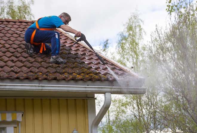 Man in Safety Harness Pressure Washing Roof