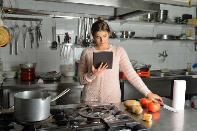 Young Woman Cooking on Stainless Steel Countertops