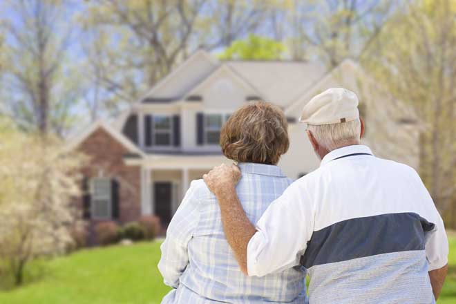 Elderly Couple Looking at the Front of Their Home