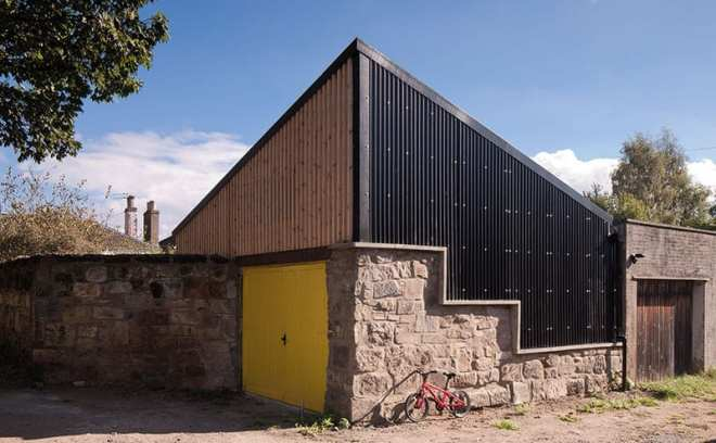 Black corrugated cladding from Cladco combines effectively with the original reclaimed stone of the old stables and the strips of larch. The pyramid shape was chosen as it gives the most space without overshadowing the neighbours.