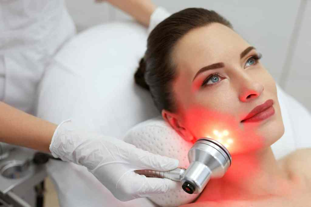 Facial Beauty Treatment. Woman Doing Red Led Light Therapy On Face Skin At Cosmetology Center.