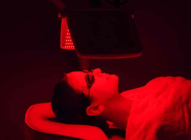 Woman receiving benefits of red light therapy through treatment.