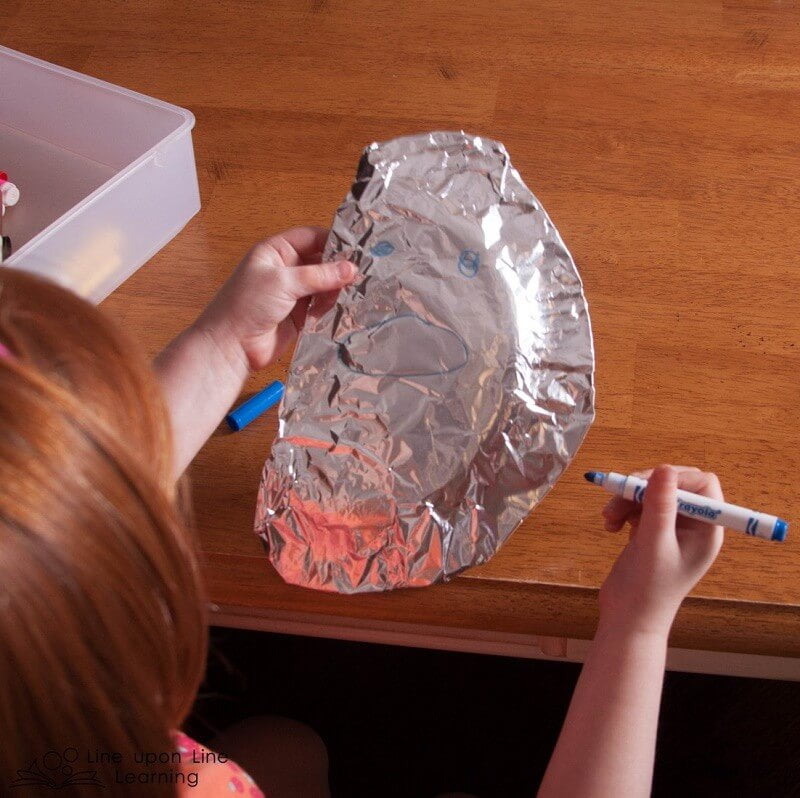 Using paper plates, we made moons: a full moon, a half moon, and a sliver moon. We wrapped them in foil and Strawberry insisted we draw faces, just as the moon had a face in the picture book we read together.