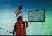 Janice has her hand on the pole that marks the Earth's Geographis South Pole.