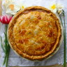 This quiche looks as delicious as it tastes: an egg wash makes the crust golden brown. It is pictured next to some daffodils and a tulip.