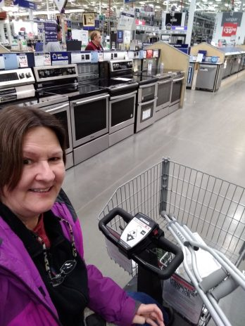 Because of my broken foot, I used an electric cart for shopping. Picture shows me in Lowe's appliance section driving an electric cart.