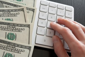Female hand counting money on computer keyboard calculator.