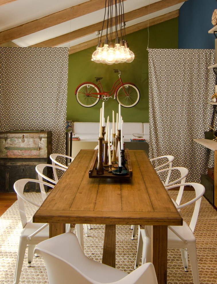 eclectic dining room idea green walls accented with hanging bike rack a cluster of light bulbs hardwood dining table white dining chairs