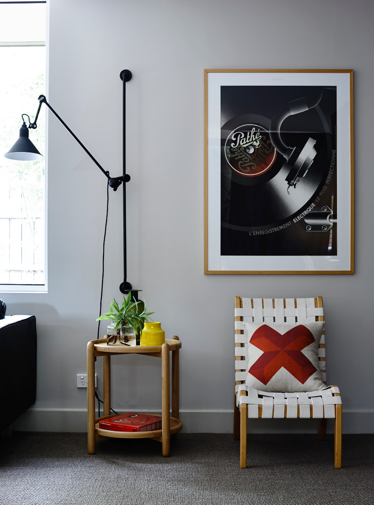 mid century modern living room idea light grey walls grey carpet wall mounted spotlight wood side table with round top small side chair with unique accent pillow