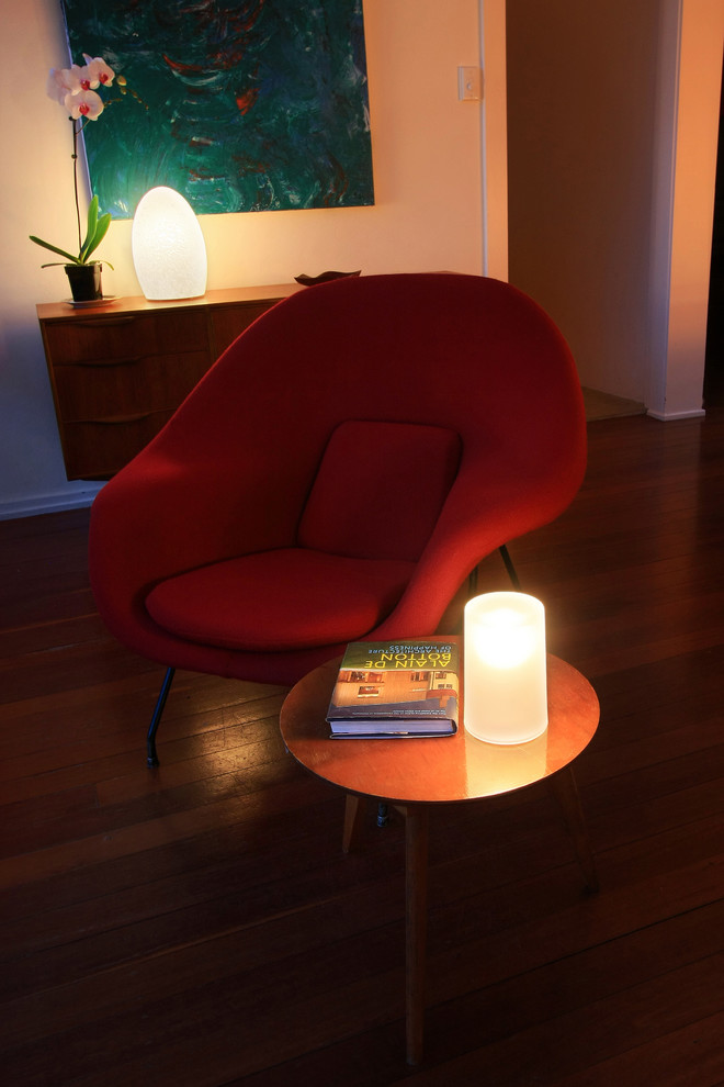mid century modern seating area low lighted table lamps bold red seat floating wood hall console potted flower decor round top wood side table
