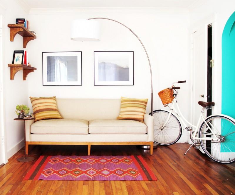 mid century modern sofa in soft cream dark toned wood floors tribal area rug white walls feminine bike decoration large floor lamp