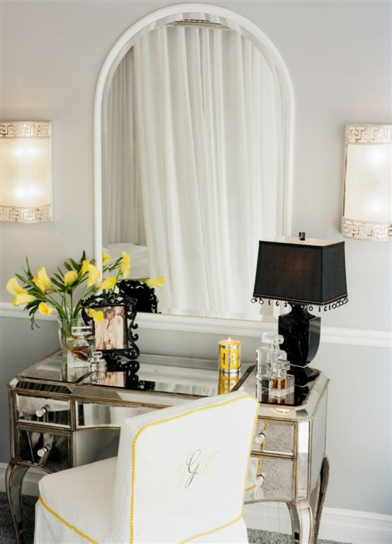 mirrored makeup vanity table with gold accents black table lamp decorative picture frames in black ornamental flowers in yellow traditional vanity chair slipcover in white curved framed vanity mirror