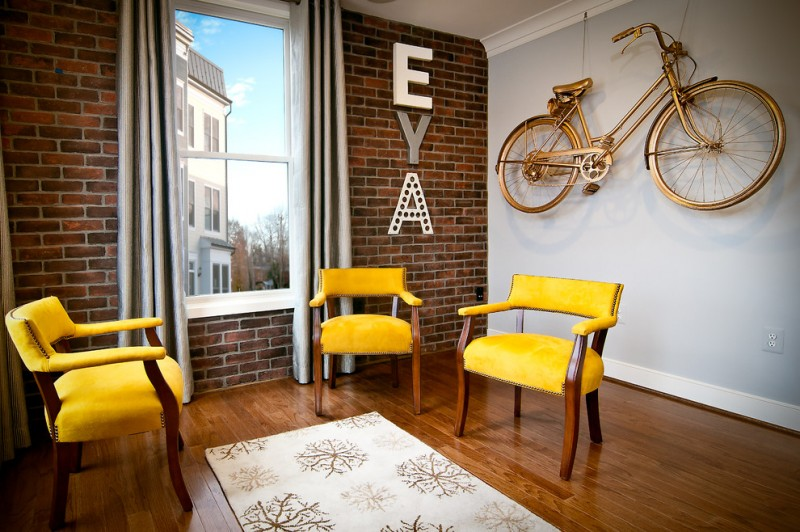 small living room idea simply yellow chairs red brick walls with centered glass window and light grey curtains gold toned bike wall ornament white wall system medium toned wood floors