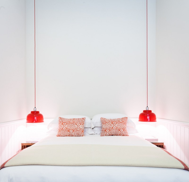 beach style bedroom idea long wired hanging pendant lights in red white bedding treatment red pillows all white walls