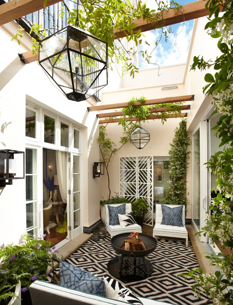 courtyard patio idea comfy white seats black wrought iron fire featrure geometric rug in black and white symmetric trellis in white amounts of greenery exposed beams glass covered lanterns