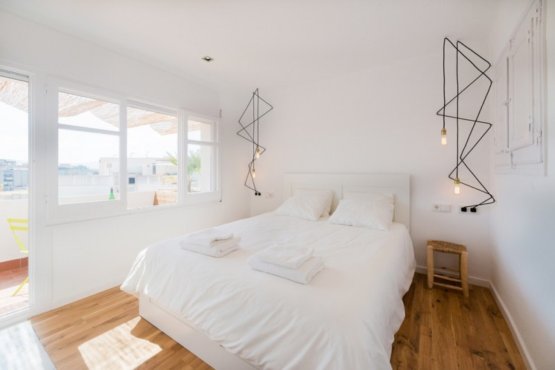 scandinavian bedroom design white bedding treatment medium toned wood floors long wired ceiling light fixtures all white walls with glass windows