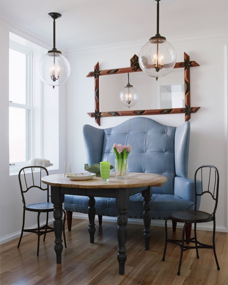 vintage style breakfast area blue sea loveseat a pair of black wrought iron chairs wood round top table wall mirror with hand carved frames glass wrapped bulb pendant lights