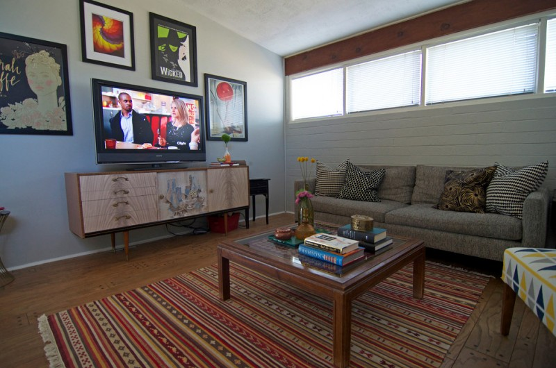 Dallas inspired family room plain toned vintage TV stand black framed paintings tribal area rug solid wood center table earthy brown sofa