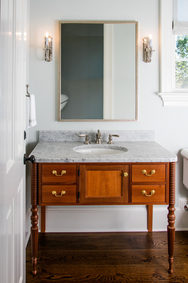 piece of vanity furniture in vintage style marble countertop undermount sink wood cabinets with drawer system dark wood floors rectangular mirror with textured gold frame candle like wall sconces