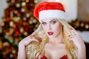 Beautiful blonde sexy Santa Clause in elegant hat and bra