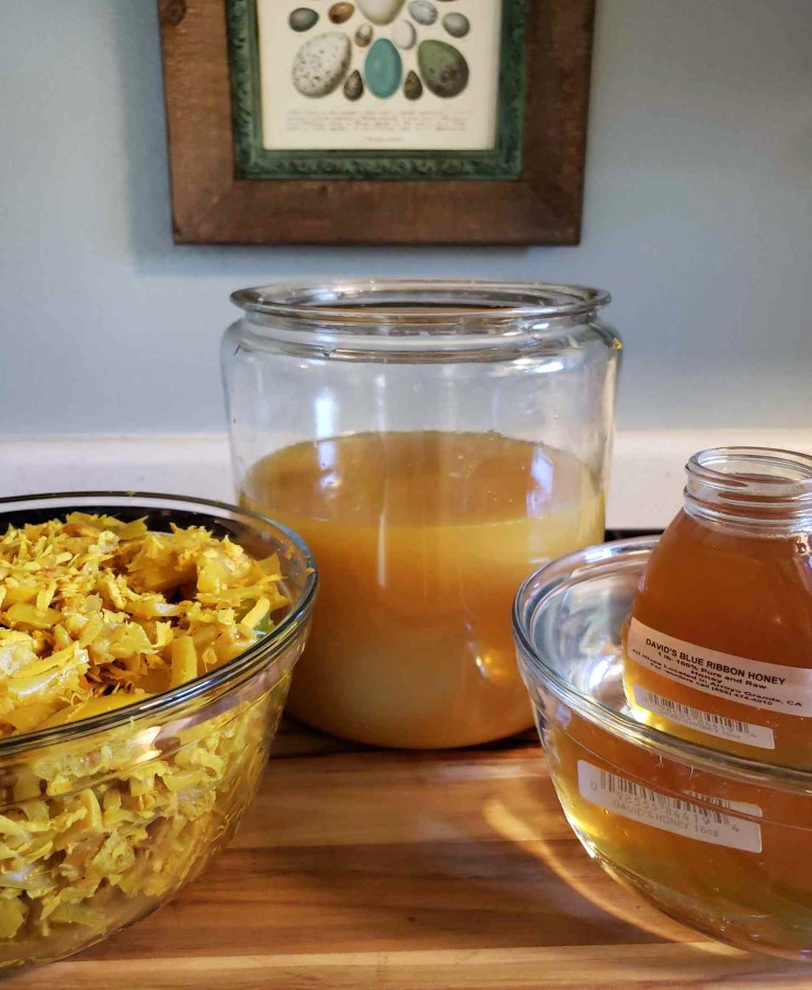 A jar of local honey is steeping sits in a glass bowl of hot water, helping to make it melt a little. This will make mixing the honey into the fire cider  easier.