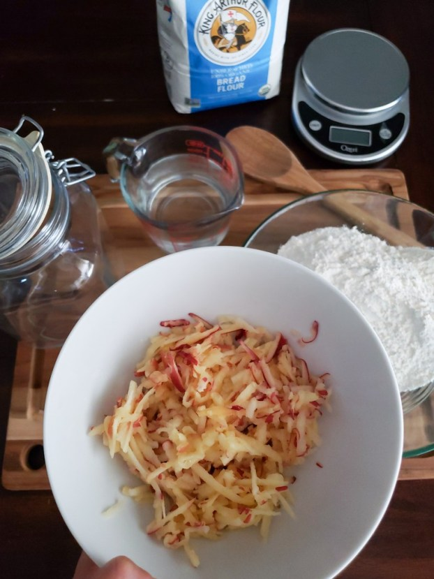 A bowl of grated organic apple is poised over a bowl or organic white bread flour, about to be combined.