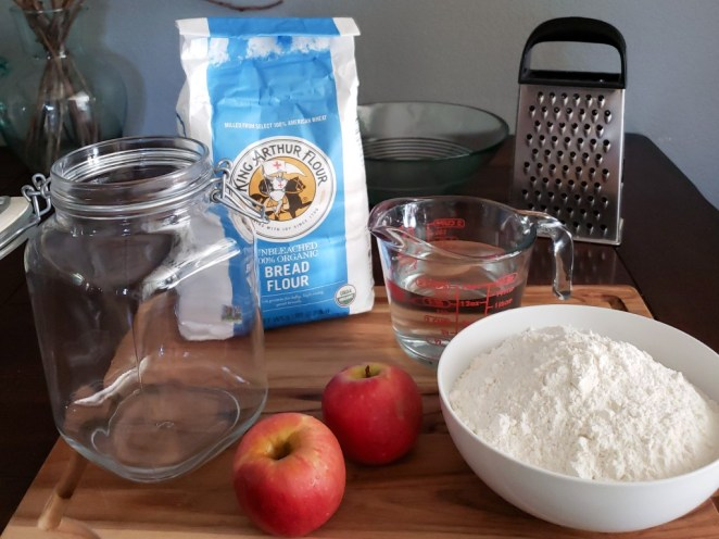 The supplies needed to make sourdough: A large glass flip-top container, 2 small organic apples, a bowl of flour, filtered water in a measuring cup, a grater to be used on the apples, a scale to weigh the flour, and a large mixing bowl to combine it all.