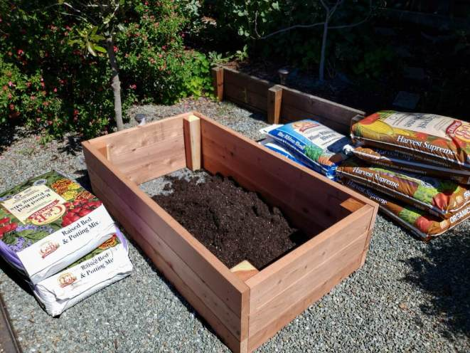 An image of an almost empty wood raised bed. It is five foot by three feet, and 18 inches deep. Various bagged soils lay around the outside of it, waiting to be added.