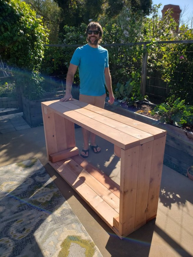 Aaron standing next to the just-built raised bed, still on the patio and on its side. He is smiling, wearing sunglasses and bright blue shirt, has dark brown hair, a short beard, and medium build. The patio garden and other raised beds (in use) are in teh background.