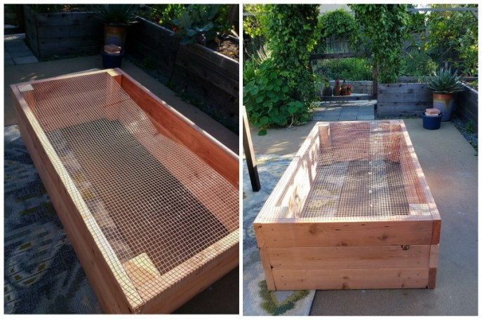 An image showing hardware cloth being attached to the underside of a garden bed. One section wasn't wide enough so another piece was added to cover it all. The bed is flipped upside down on the patio.