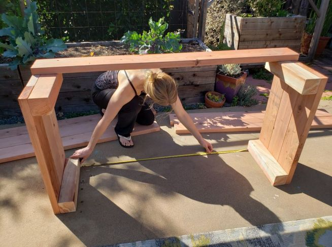 DeannaCat is shown kneeling down taking a measurement of a partially made wooden raised garden bed. Constructing garden beds and structures may be a necessity when on decides to start a homestead.
