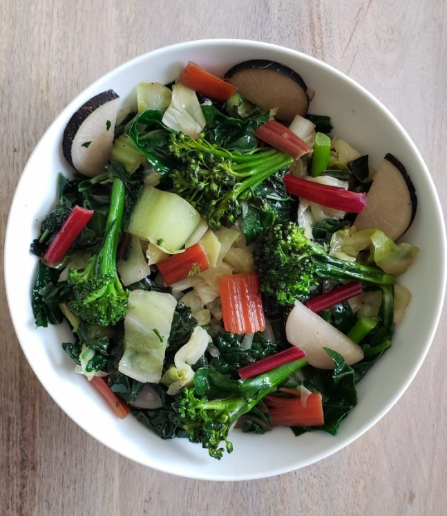 A while bowl shown from above, full of cooked homegrown cabbage, kale, Spanish black radishes, broccoli, swiss chard, and mustard greens. There are curry lentils below the veggies.