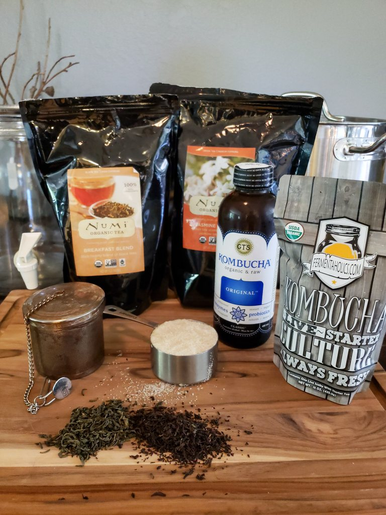 The supplies needed for primary ferment, including tea, sugar, a SCOBY, a bottle of plain kombucha, a large stainless steel pot, and a glass dispenser.