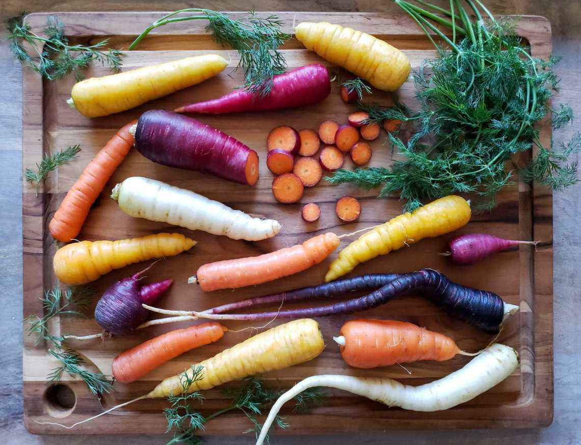 rainbow carrots on a cutting board with sprigs of fresh dill around them