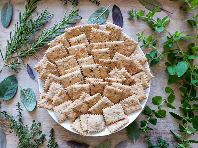 A plate full of freshly baked herbed sourdough crackers. There are various fresh herbs surrounding the plate such as thyme, rosemary, sage, and oregano. With a kitchen herb garden, adding fresh herbs to any recipe is a breeze.