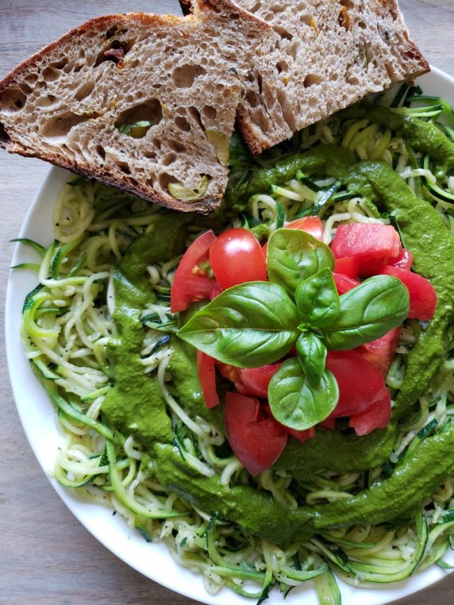 The final plating of zoodles is shown on a plate which contains a bed of zoodels, drizzled with fresh pesto, a nice pile of fresh tomatoes is placed in the middle of the pile along with a sprig of basil. Two slices of fresh sourdough bread are sitting on the edge of the plate.