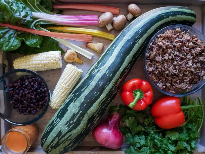 A photo of the raw ingredients used in this recipe, artfully laid out on a tray. A huge green striped zucchini lays in the middle, surrounded with red bell pepper, red onion, cilantro, brown wild rice and black beans in bowls, ears of white corn, garlic cloves, and leaves of swiss chard.