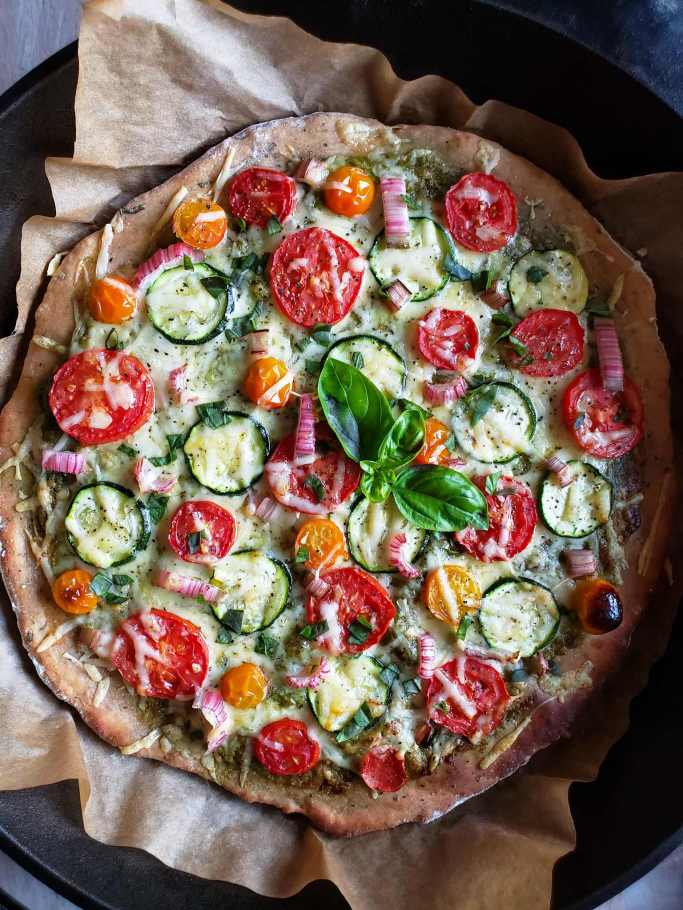 A close up photo of the finished pizza. The parchment paper is poking up from around the crust, and there is now chopped basil lightly spread across the pizza surface with a sprig of basil sitting in the middle. You can now see some of the tomatoes have blackened from the bake and the edges of the pizza crust look crispy brown.