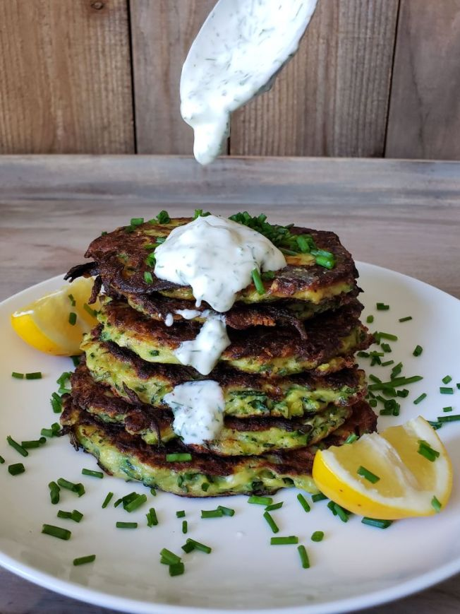 A white plate has a stack of six crispy golden brown zucchini fritters sitting in the middle of it. The plate is garnished with chopped chives and two wedges of lemon. There is a spoon coming in from the top of the image that has dolloped some of the yogurt sauce on top of the fritters and some of the sauce has slid down the front side of the stack of fritters as well.