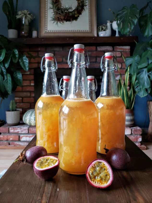 """Five quart size EZ Cap bottles are sitting on a long, skinny coffee table. There are three passionfruit placed around the front of the bottles with one of them being cut in half, displaying its pulpy, tropical goodness. You can faintly read the writing on one of the bottles which labels the flavor as """"Passionfruit."""" The liquid is golden to slight red guava in color."""